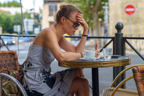 woman at cafe with newspaper