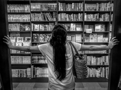 woman facing bookshelves
