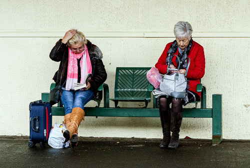 women at train station bench